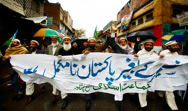 Supporters of religious political party Jamaat-i-Islami (JI) chant slogans during a rally to mark Kashmir Solidarity Day in Peshawar. The banner reads in Urdu: ?Pakistan is incomplete without Kashmir?.