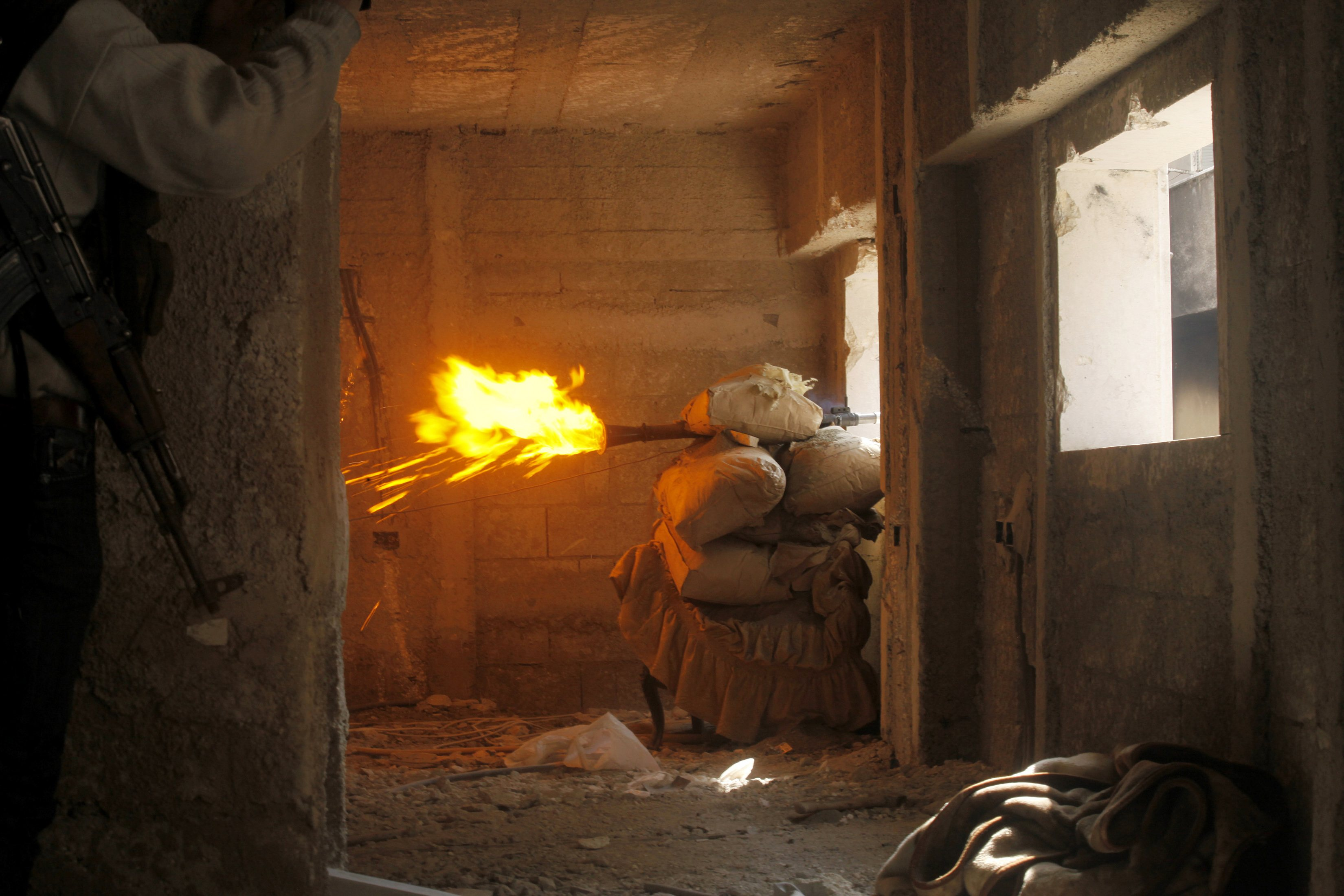 Free Syrian Army fighters take cover while firing a rocket on the front line in Izaa district in Aleppo.?Photo by Reuters