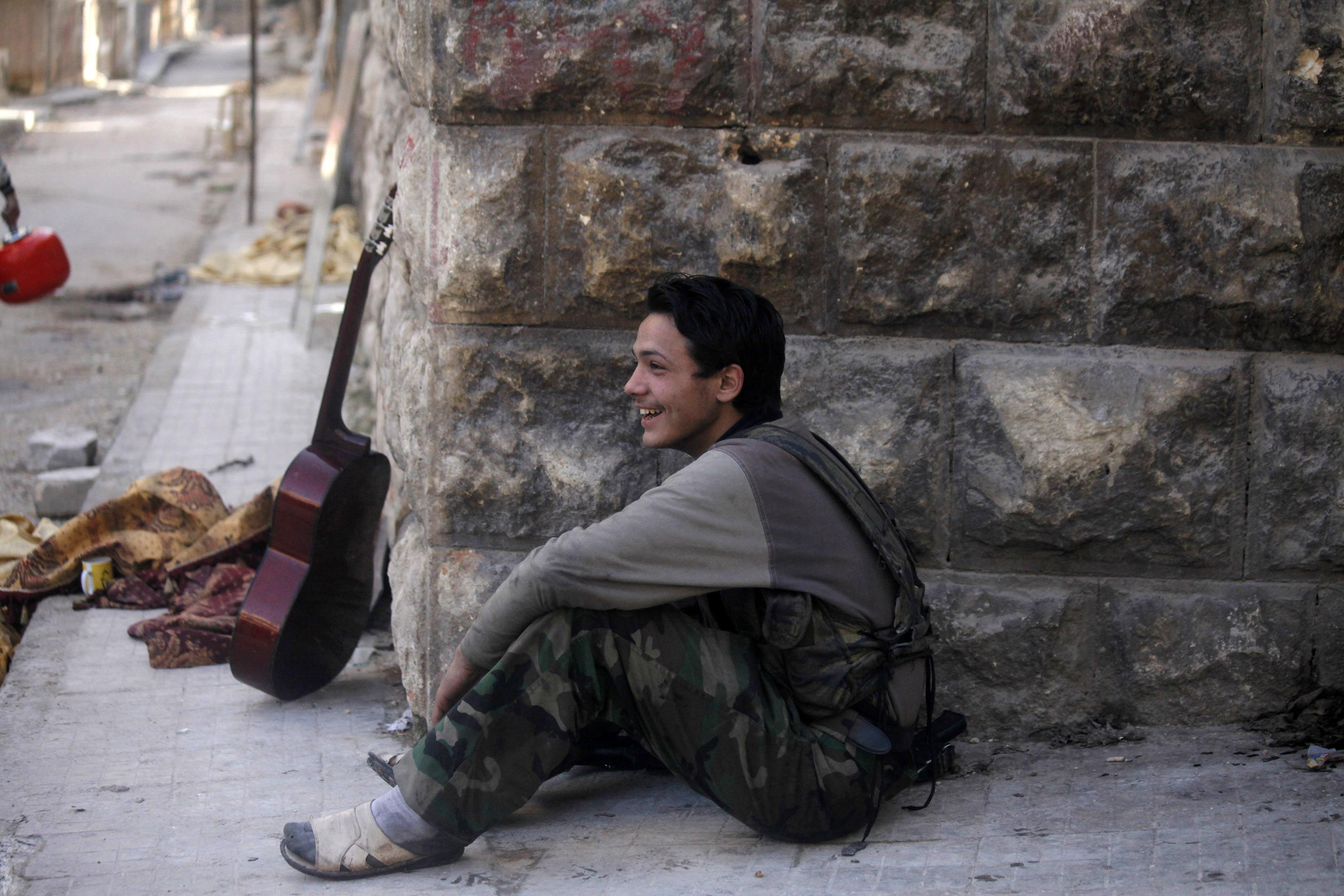A Free Syrian army fighter rests beside a guitar in Izaa district in Aleppo.?Photo by Reuters