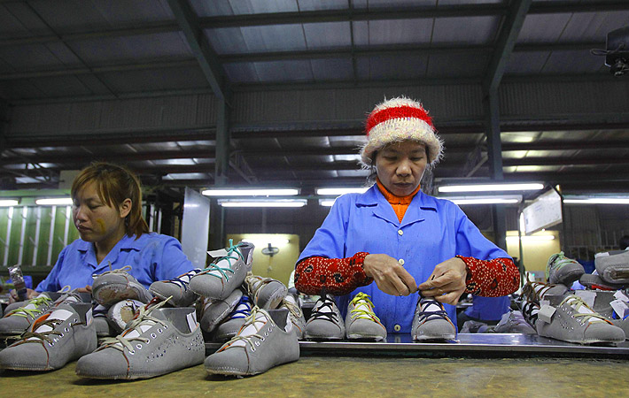 Employees work on an assembly line at a shoe factory in Tan Lap village, outside Hanoi.  Vietnam has approved a broad plan to boost its economy to 2020, focusing on restructuring public investment, banks and state-owned enterprises while controlling inflation and maintaining growth.