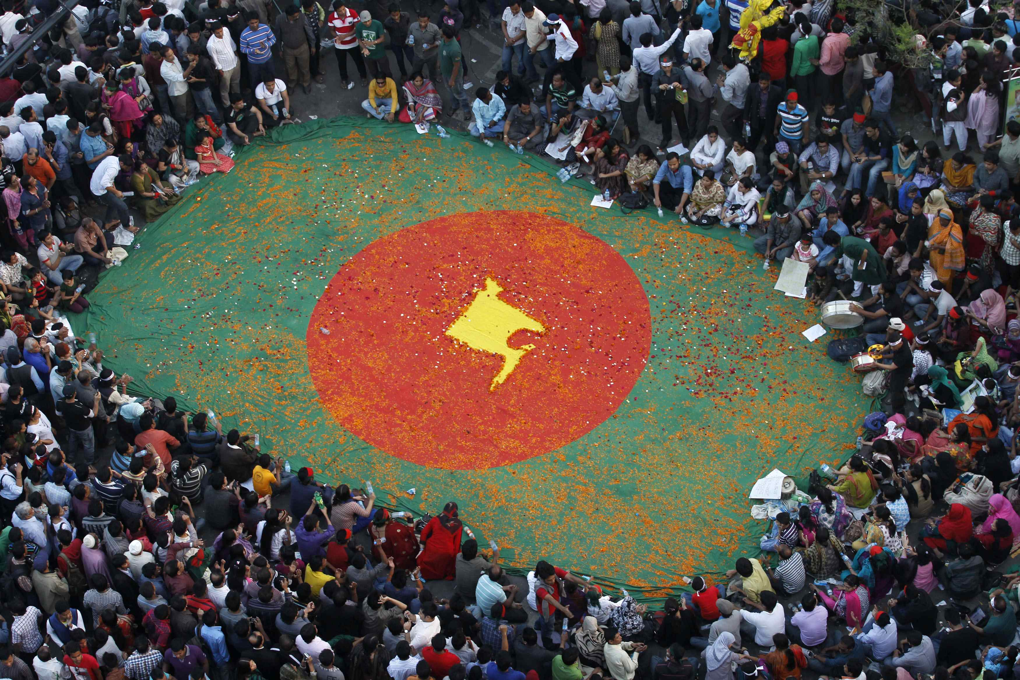 People observe a sit-in protest around a national flag of Bangladesh with a map of the country on it, made by flowers, as they attend a mass demonstration at Shahbagh intersection, demanding capital punishment for Bangladesh's Jamaat-e-Islami senior leader Abdul Quader Mollah, after a war crimes tribunal sentenced him to life imprisonment, in Dhaka February 9, 2013. — Photo Reuters