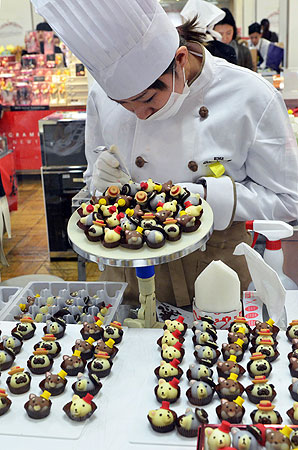 A chocolatier of Japanese sweet shop Goncharoff puts the finishing touches to animal-shaped chocolates at Tokyo's Takashimaya department store. —Photo by AFP