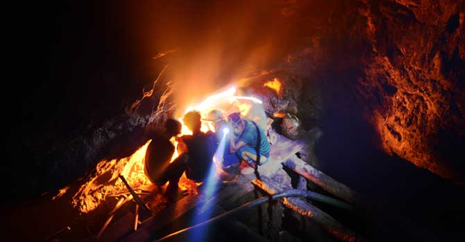 Indian coal miner, Surya Limu (inside hole), squats with other miners by a fire to keep warm hours before dawn, inside the face of a 50 meter deep shaft in Rymbai village in the northeastern state of Meghalaya. Unlike his more experienced colleagues, Limu moves slowly down the precarious mine steps, his delicate features straining with the effort. Child labour is officially illegal in India, with several state laws making the employment of anyone under 18 in a hazardous industry a non-bailable offence.  -Photo by: AFP