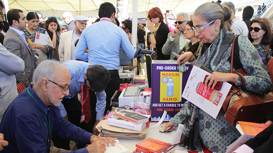Irshad Abdul Kadir signs copies of his book 'Clifton Bridge' on the third day of the Karachi Literature Festival. -Photo by Alisia Pek/Dawn.com