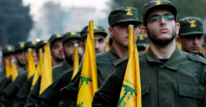 In this November 12, 2010 file photo, Hezbollah fighters hold their party flags, as they parade during the opening of new cemetery for colleagues who died in fighting against Israel, in a southern suburb of Beirut. -AP Photo