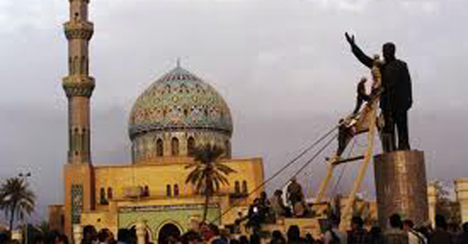 Protesters tie ropes around Saddam Hussein's statue in Baghdad to pull it down, 2003.