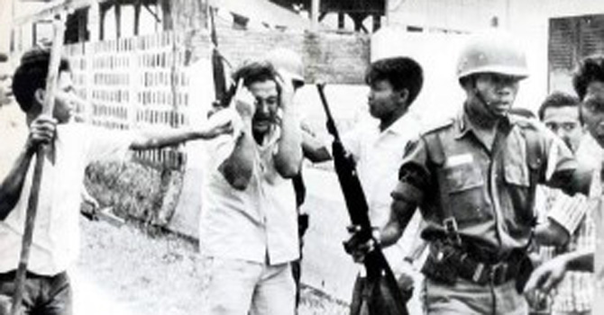 A communist student at the Jakarta University being roughed up by soldiers and Islamic student activists during the military's purge against leftists in Indonesia in 1965.