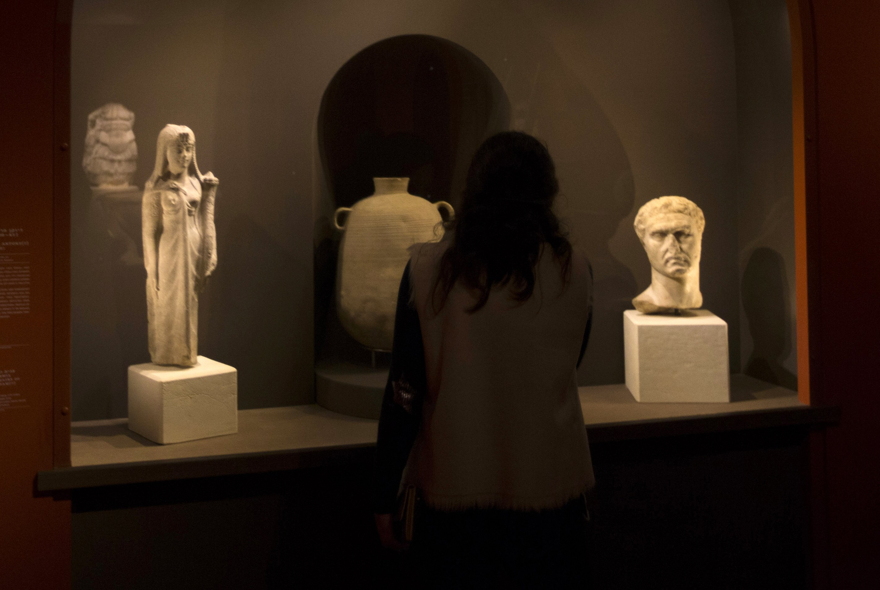 "A woman looks at archaeological artifacts during a media preview of an exhibition titled ""Herod the Great: The King's Final Journey"". — AFP Photo"