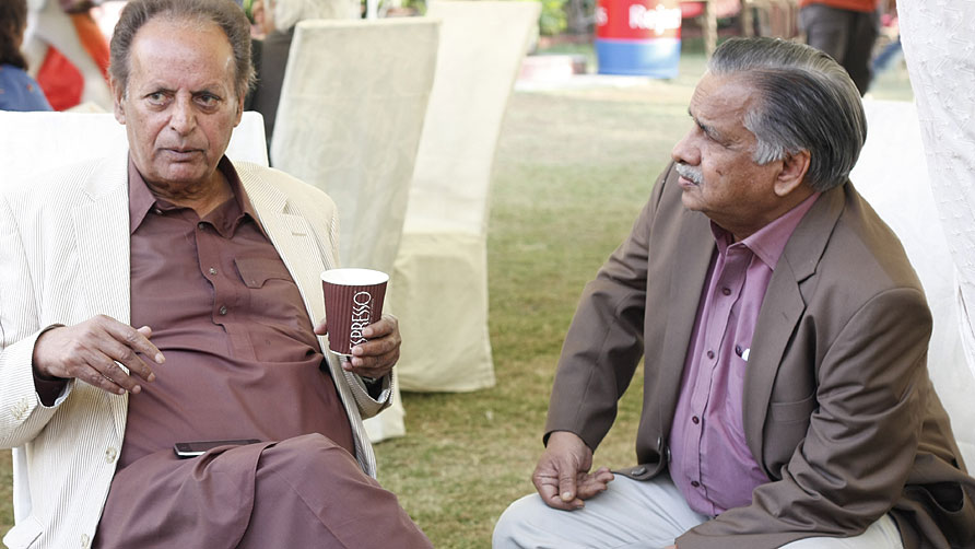 Mustansar Hussain Tarar chats with Mujahid Barelvi. - Photo by Eefa Khalid/Dawn.com