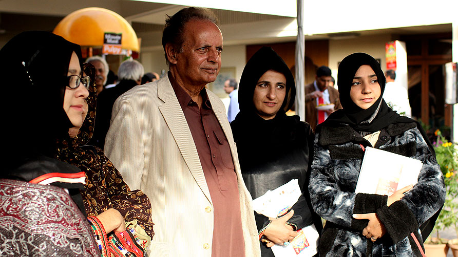 Mustansar Hussain Tarar posing for a photograph with a few fans. - Photo by Sara Faruqi/Dawn.com