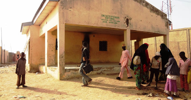 People loiter around the Haye dispensary on February 8, 2013 in the northern Nigerian city of Kano, where gunmen on motorised tricycle killed seven female polio immunisation workers. Ten polio immunisation workers, nine of them women, were killed and five others injured in separate gun attacks on two polio clinics in the city. — Photo by AFP