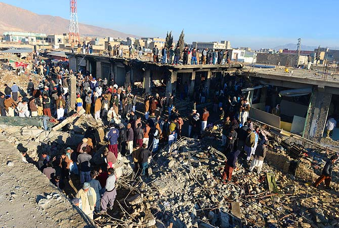 People are pictured amid debris at the scene of yesterday's bomb attack site in Quetta.