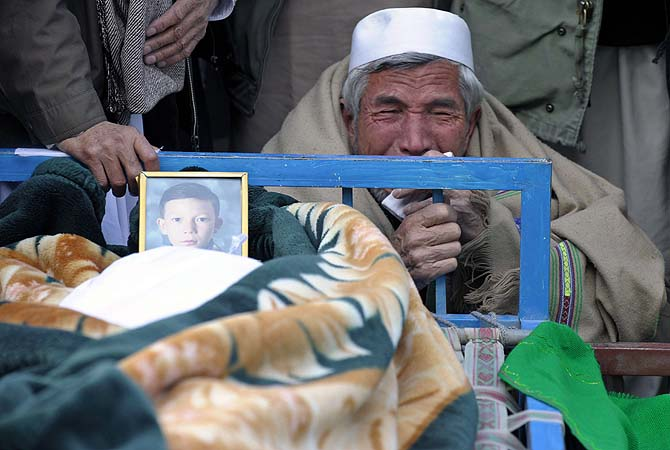 Man mourns in front of the coffin of his son as he gathers along with others during a protest against the killing of bomb attack victims in Quetta.