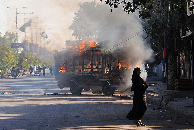 A passengers bus, set alight be demonstrators in retaliation of yesterday's bomb attack in Quetta, burns as a pedestrian walks past in Karachi.