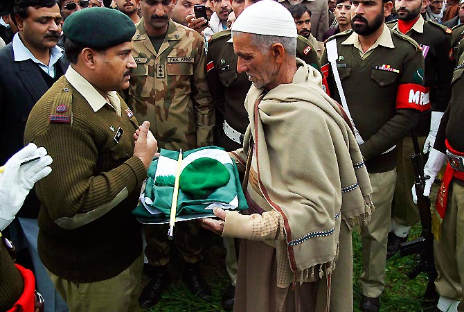 A military official hands over a Pakistan military cap, stick and national flag to the father of Pakistani soldier Muhammad Akhlaq, whom the Pakistan military said was killed by Indian soldiers. -Photo by Reuters