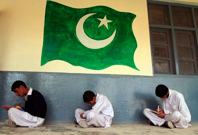 Students sit near an image of Pakistan's national flag during class at the Musa Neka Public School in Wana, the main town in Pakistan's South Waziristan tribal region bordering Afghanistan November 28, 2012. - Photo by Reuters