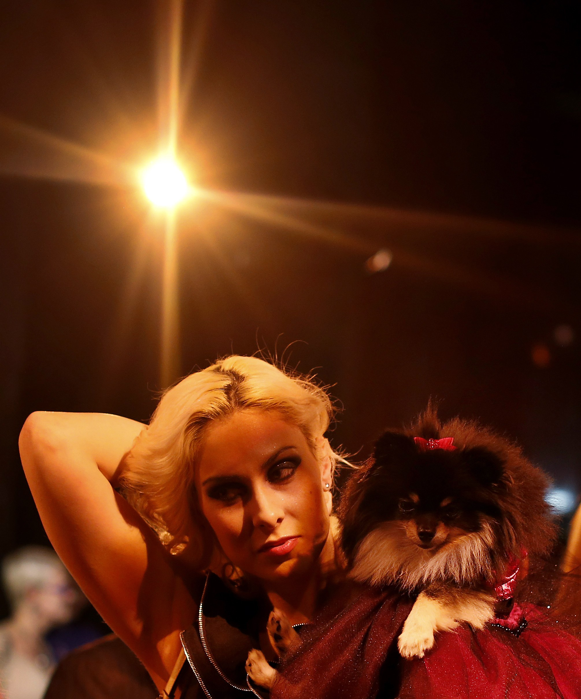 Victoria Viscardi brushes back her hair while holding her dog Gia Marie, a Pomeranian breed, before the start of the New Yorkie Runway Doggie Fashion Show in New York. ? Reuters Photo