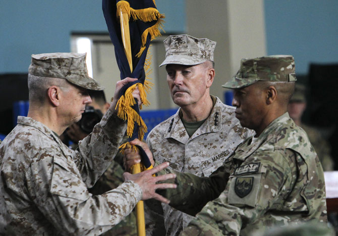 Outgoing International Security Assistance Force (Isaf) commander General John Allen (L) hands over a flag to US General Joseph Dunford during a change of command ceremony at the Isaf headquarters in Kabul on February 10, 2013. US General Joseph Dunford assumed command of Nato forces in Afghanistan on Sunday, taking over from General John Allen as the coalition prepares to withdraw the bulk of its combat troops by next year. - Photo by AFP