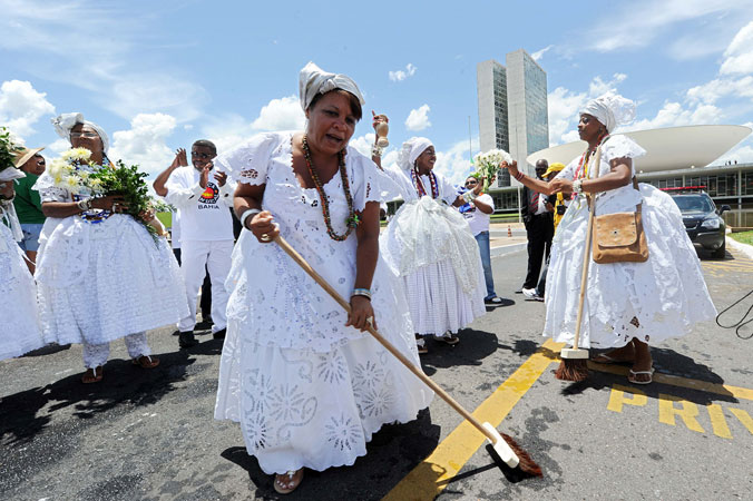 A group of Baianas wearing traditional clothes make ?a cleaning? against negative energies and corruption before the National Congress during the 7th March of the Workers Unions and Social Movements in Brasilia. ?Photo by AFP