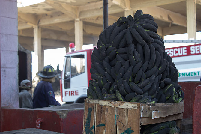 Fire men work outside a fruit shop at New Sabzimandi. In the foreground burnt bananas lie in a pile.