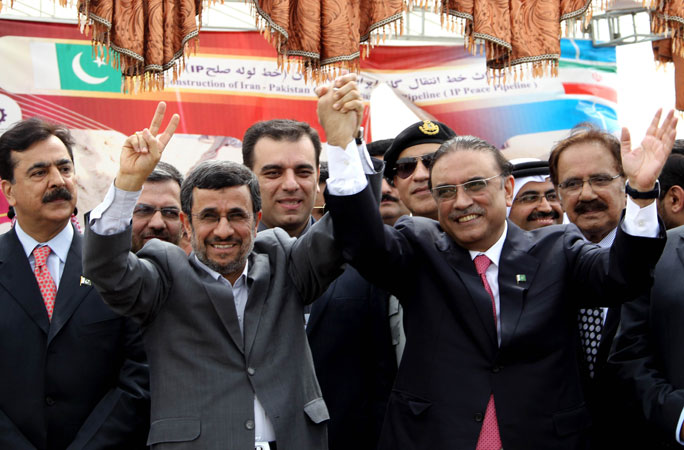 Iran's President Mahmoud Ahmadinejad (2nd L) and Pakistan's President Asif Ali Zardari wave during a ceremony marking the start of work on the 780-kilometre (485-mile) pipeline from Iran to Pakistan in the Iranian border city of Chah Bahar. ?Photo by AFP