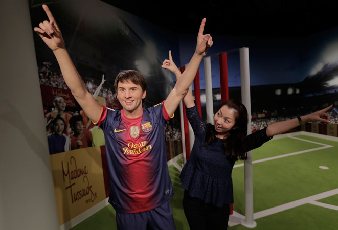 A visitor poses with the wax figure of Lionel Messi. ?Photo by AP