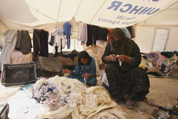 Syrian refugee women work at her second hand clothes shop at the Al Zaatri refugee camp in the Jordanian city of Mafraq.  ?Photo by Reuters