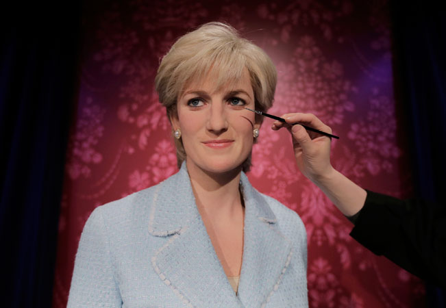 A figure production maintenance staff retouches the wax figure of princess Diana. ?Photo by AP