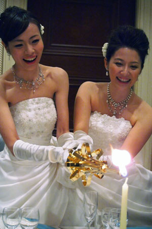 Lesbian couple Koyuki Higashi (L) and Hiroko lighting a candle at their wedding reception in Tokyo. They are the first gay couple to tie the knot at Tokyo Disney Resort, both decked out in fairytale white dresses despite an initial ruling that one had to wear men's clothes.  ?Photo by AFP
