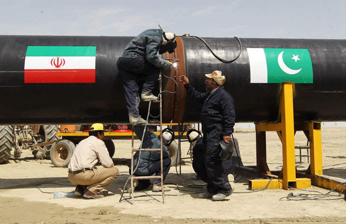 Iranians work on a section of a pipeline after the project was launched during a ceremony with presidents of Iran and Pakistan. ?Photo by AFP
