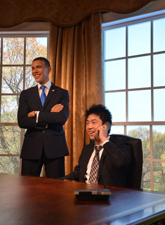 A Japanese man uses a phone next to the wax figure of US President Barack Obama. ?Photo by AFP