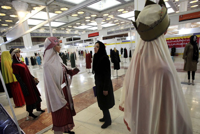 An Iranian woman looks at outfits on mannequins, during the ?Second Fadjr International Fashion and Clothing Festival? at the Imam Khomeini grand mosque, in Tehran, Iran. Iran's strict Islamic dress code for women, enforced after 1979 Islamic Revolution, requires them to cover their hair and bodies in public. ?Photo by AP