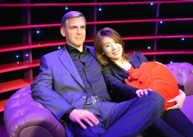 A woman sits with the wax figure of Hollywood star George Clooney. ?Photo by AFP