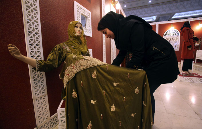 An Iranian woman adjusts a mannequin during the ?Second Fadjr International Fashion and Clothing Festival?. ?Photo by AP