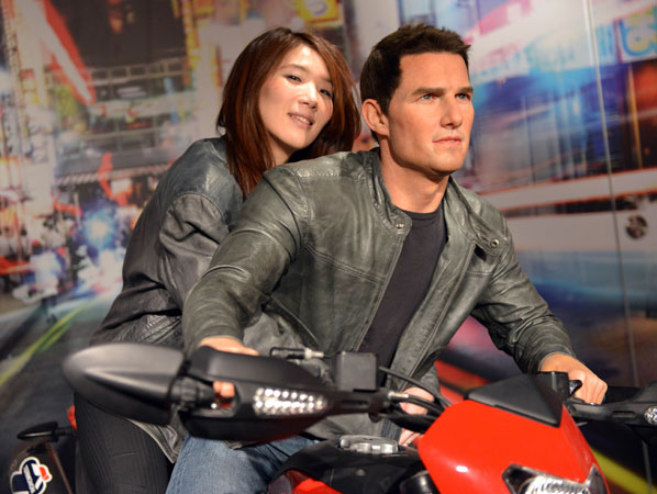 A woman sits on a motorbike with the wax figure of Hollywood star Tom Cruise. ?Photo by AFP