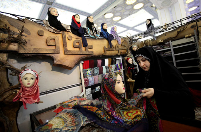 An Iranian woman dresses a mannequin with a head scarf, during the ?Second Fadjr International Fashion and Clothing Festival?. ?Photo by AP