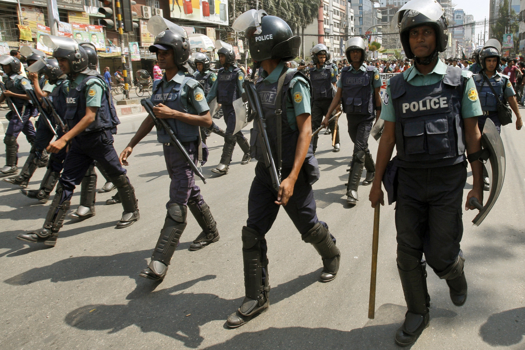 Riot policemen escort Bangladeshis protesting against a strike called by Jamaat-i-Islami activists to denounce the trial by a special tribunal involving several of their leaders in Dhaka. ? Photo by AP