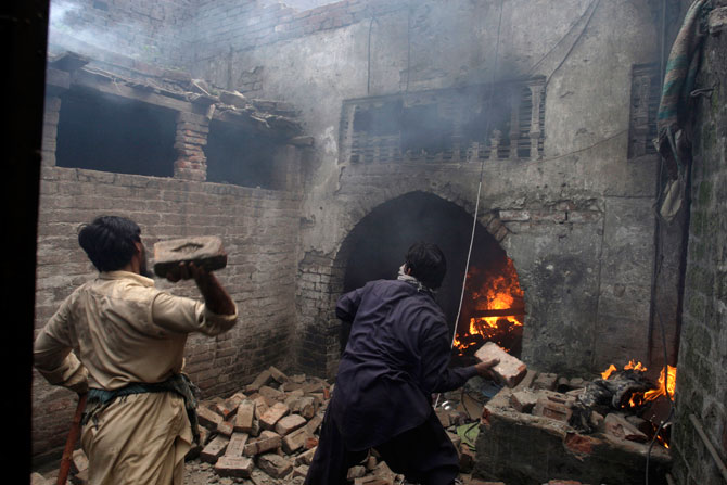 Men, part of an angry mob, throw bricks at a Christian house after setting it on fire, Lahore, March 9, 2013.