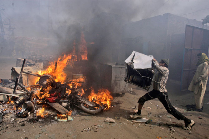 A man, part of an angry mob, throws items taken from Christian houses into a fire in Lahore, March 9, 2013.