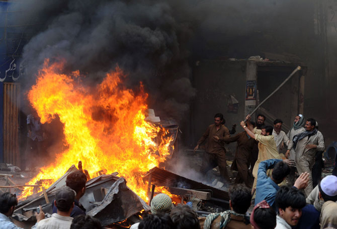 Angry demonstraters torch Christians' belongings during a protest over a blasphemy row in a Christian neighborhood in Badami Bagh area of Lahore on March 9, 2013.