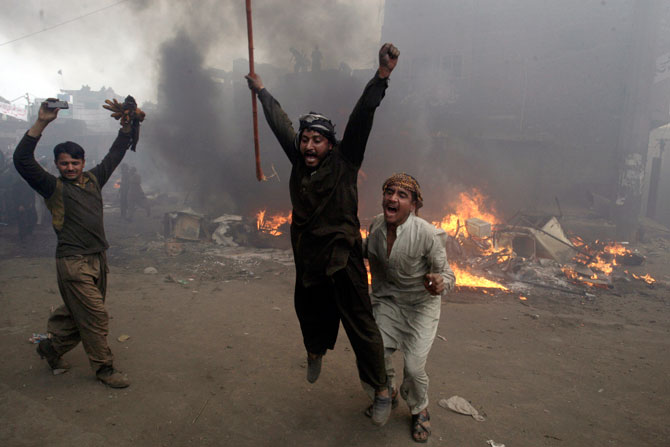 Men, part of an angry mob, react after burning belongings of Christian families, Lahore, March 9, 2013.