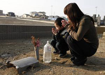 Yuko Sugimoto and her son Raito pray at the site where their pet dog was buried in the yard of their house in Ishinomaki. —Photo (File) Reuters