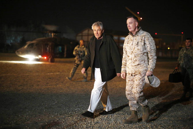 US Secretary of Defense Chuck Hagel (C) steps off his helicopter with US Marine General Joseph Dunford (R), Commander of the International Security Force upon Hagel's arrival near Camp Eggers in Kabul, Afghanistan, on March 8, 2013. - Photo by AFP