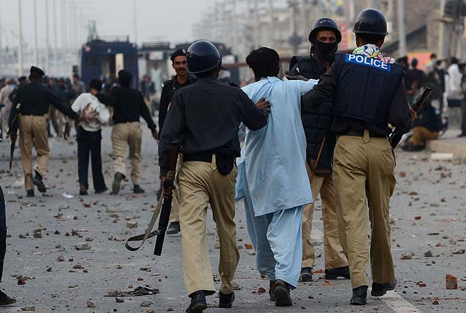 Policemen detain demonstrators during a protest against the attack on the homes of members of the Christian community by demonstrators in Lahore on March 10, 2013. ? Photo by AFP