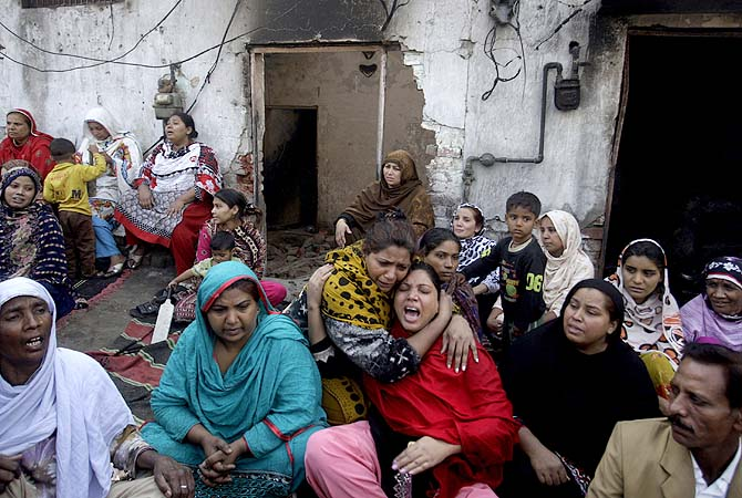 Women wail after visiting their homes which were destroyed by an angry mob in Lahore, March 10, 2013. ? Photo by AP