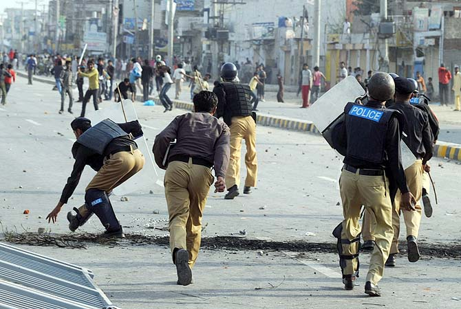 Policemen chase demonstrators during a protest against the attack on the homes of members of the Christian community by a mob in Lahore, March 10, 2013. ? Photo by AFP