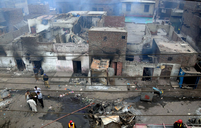 Pakistani police officials examine the burnt out houses of members of the Christian community attacked by Muslim demonstrators during a protest over alleged blasphemous remarks by a Christian in a Christian neighborhood in Badami Bagh area of Lahore on March 9, 2013. - Photo by AFP