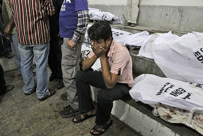 A man reacts next to the body of a relative who was killed in a bomb blast, at a hospital's morgue in Karachi, Pakistan, Sunday, March 3, 2013.?Photo by AP