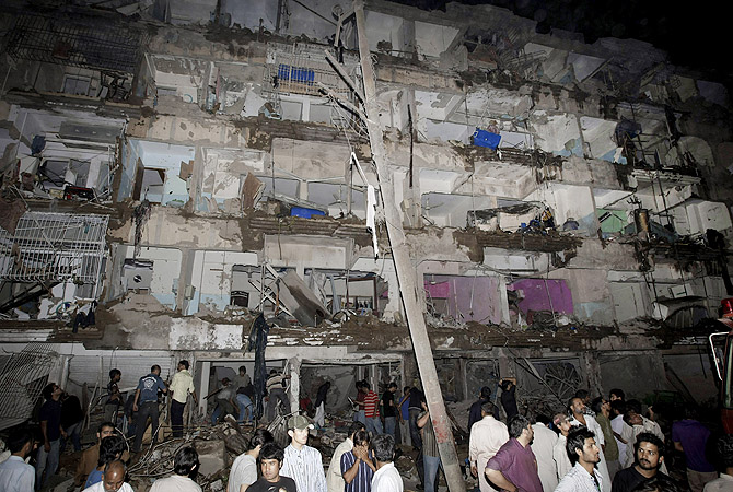 People gather at the site of a bomb blast in Karachi, Pakistan, Sunday, March 3, 2013.?Photo by AP
