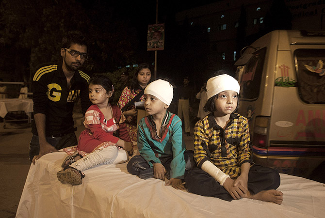 Children, who were slightly injured in a bomb blast, are brought to a hospital in Karachi, Pakistan, Sunday, March 3, 2013. Officials say a bomb blast has killed dozens of people in a neighborhood dominated by Shia Muslims in the southern city of Karachi.?Photo by AP
